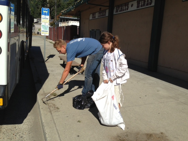 BCBA Board member Justin Acton and a young volunteer clean the sidewalks by Johnny's Market
